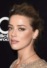 Amber Heard kept her beauty look subtle with neutral eyeshadow and a pale lip.