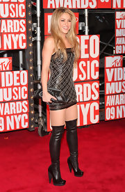 Shakira turns on the sex appeal in thigh-high latex boots and a mini dress at the MTV VMAs.
