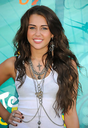 Teen Queen Miley Cirus loves to layer on tons of necklaces which she shows us here can really transform a plain white tank top.
