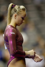 Nastia matches her ponytail holder perfectly with her uniform.