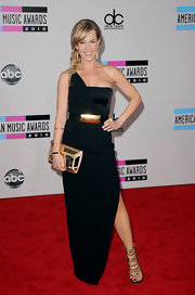 Julie wore a classic floor length black dress made modern with a gold logo belt and boxy clutch.