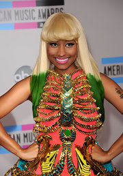 Niki Minaj was all smiles on the red carpet of the American Music Awards donning an asymmetrical blond bob. The rapper/singer dipped the ends in green dye.