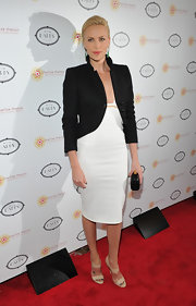 Charlize wears a lovely black evening blazer over a low-cut white cocktail dress for a sophisticated look.