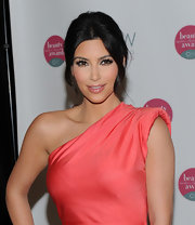 Kim K. paired her coral dress with a loose center part bun.