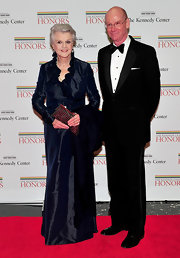Angela Lansbury carried a glitzy clutch with an elegant long sleeved navy dress.