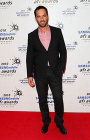 Alex wore a classic black suit on the red carpet. He paired his look with a colorful pink button down.