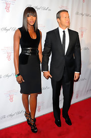 Naomi Campbell paired her chic black dress with daring leather platform sandals complete with metal detailing.