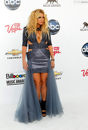 The music industry's resident party girl Ke$ha hit the white carpet in a blue satin mini dress with bold shoulders and daring cut-outs. The Tik Tok singer's futuristic glittery dress featured an inexplicable tulle train. Glittery cheek and eye makeup rounded out Ke$ha's look.