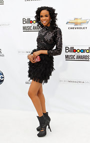 Michelle Williams added an edge to her frilly sequined dress with black leather mid-calf boots with cut-outs.