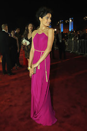 Freida Pinto added sophistication to her stunning fuchsia dress with a simple gold-trimmed box clutch.