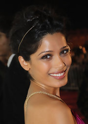 Freida Pinto added a sweet golden headband to her lovely updo at the 2011 Doha Tribeca Film Festival.