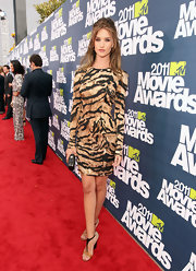 Rosie Huntington-Whiteley paired her exotic cocktail dress with a gold metal minaudiere with black leather details.