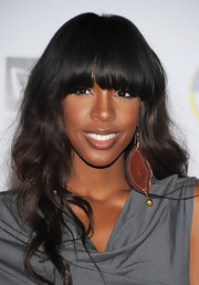 Kelly Rowland wore a burnt orange gemstone earring while attending the Maxim Hot 100 party.