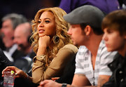 Beyonce Knowles sat court side at the NBA All-Stars game wearing 18-karat gold and silver oval earrings with diamonds.