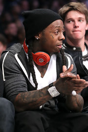 Lil Wayne buncedl up in a hoodie and black knit beanie for the NBA All-Star game.