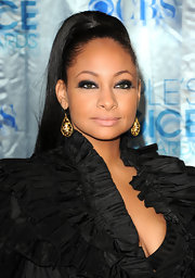 Actress Raven Symone added a sultry touch to her sleek ponytail with a classic smoky lid. She cleverly opted for an otherwise neutral look complete with a nude lip and bronzed glow.