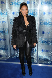 Raven takes wearing black on the red carpet to a whole new level! Here she wears a ruffled black evening jacket with thigh high boots and a black leather belt.