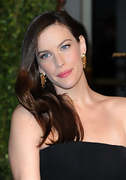 Liv Tyler paired her strapless neckline with gold and gemstone earrings at the 2011 Vanity Fair Oscar party.