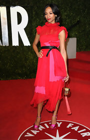 Zoe Saldana added exotic flair to her 'Vanity Fair' Oscar party look with a gold hard case Tassel clutch.
