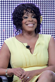 Niecy pulls her curls back into a low up 'do with her signature hair flower.