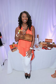 Toccara Jones wore a vibrant coral top with a pair of white skinny pants.