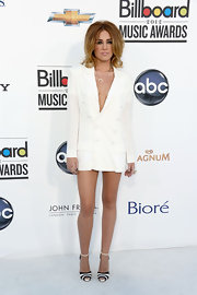 Miley Cyrus paired her bright white jacket with graphic black and white striped sandals.