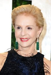 Carolina Herrera complemented her feathered dress with a pair of dangling decorative earrings at the 2012 Vanity Fair Oscar party.