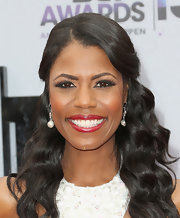 Omarosa opted for a ruby red lipstick to show off her pearly white.