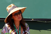 A large straw hat shielded Tia Carrere's face from the sun as she watched the 2013 BNP Paribas Open.