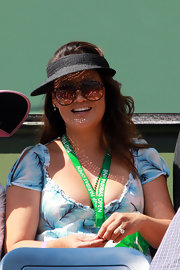 Tia Carrere watched the BNP Paribas Open wearing a black straw sun visor and oversized sunglasses.