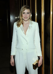 A gold box clutch added shimmer and elegance to Greta Gerwig's look during the CFDA Fashion Awards after-party.