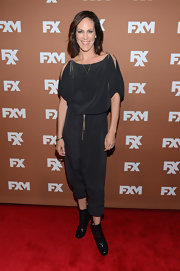 Annabeth Gish chose a loose jumpsuit with shoulder slits for her casual but edgy red carpet look.