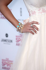 Emily Osment opted for a fun and funky set of gold and silver bangles with turquoise detailing for her evening look.