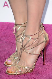 Nina Dobrev opted for gold strappy sandals to top off her look at the Independent Spirit Awards.