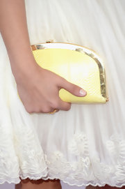 A yellow frame clutch added a touch of color to Stella Maeve's look at the Independent Spirit Awards.