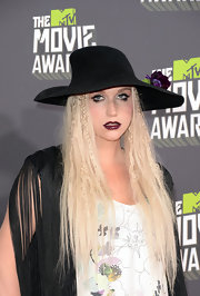 Kesha topped off her retro-inspired red carpet look with a wide-brimmed hat that featured a purple floral accent.