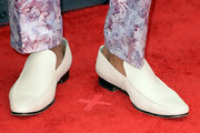 RuPaul kept his footwear fairly simple with a pair of white leather slip ons.