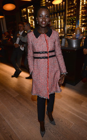 Lupita Nyong'o arrived at the Grey Goose Vodka dinner wearing a chic Moschino tweed coat with black leather bow accents.