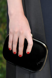 Greta Gerwig accessorized with a simple yet elegant black velvet clutch at the 2013 Vanity Fair Oscar party.