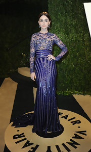 Lily Collins chose a beaded, long sleeve violet gown with an embroidered bodice and open back for her Oscar look.