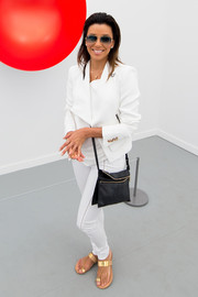 Eva Longoria contrasted her white outfit with a black crossbody bag by Victoria Beckham.