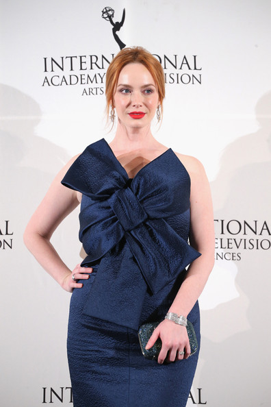 Christina Hendricks paired a glittery blue clutch with a bow-embellished strapless dress for the International Emmy Awards.