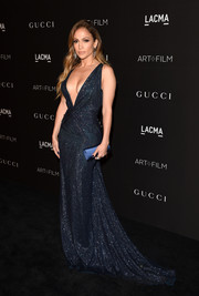 Jennifer Lopez made a dazzling appearance at the LACMA Art + Film Gala in a crystal-embellished midnight-blue gown by Gucci Premiere, boasting a long train and a down-to-there neckline.