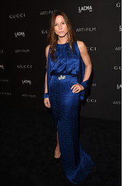Rhona Mitra attended the LACMA Art + Film Gala wearing a royal blue silk gown with a front slit and split sleeves.