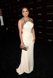 Salma Hayek chose a nude satin clutch, also by Gucci, to pair with her gown.