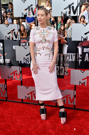 Iggy Azalea sported a curvy silhouette in a body-con, blush-colored John Galliano dress, featuring an embellished mesh-panel bodice, during the MTV Movie Awards.