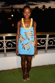 Lupita Nyong'o chose the perfect summer get-up for day 4 of the Maui Film Festival, a turquoise Fausto Puglisi shift dress with gold palm tree beading.