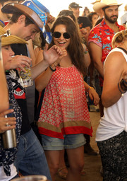 Mila Kunis paired her top with faded denim shorts.