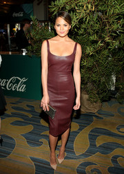 Chrissy Teigen teamed her dress with a simple yet elegant silver Jimmy Choo clutch.