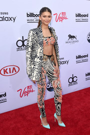 Zendaya Coleman brought a burst of energy to the Billboard Music Awards red carpet with this mixed-print pantsuit and bra top ensemble by Fausto Puglisi.